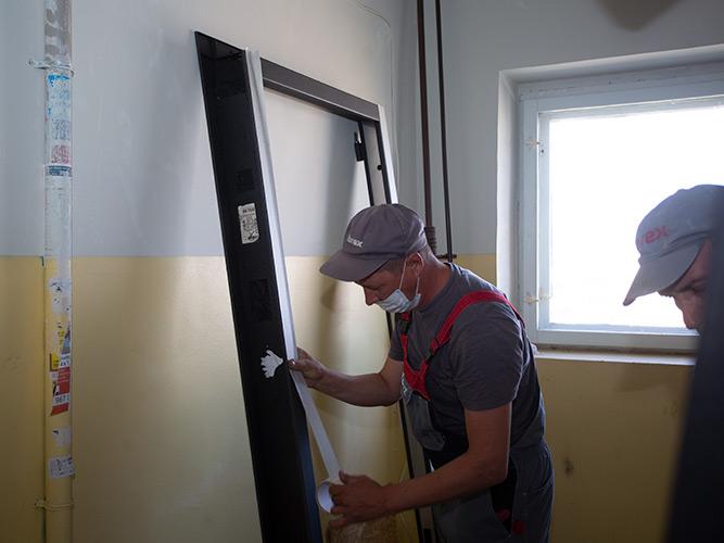 Наклеивание малярной ленты на дверной короб перед установкой